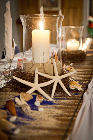 Beach theme wedding bridal table with candles, starfish, sand and shells Stock Photo
