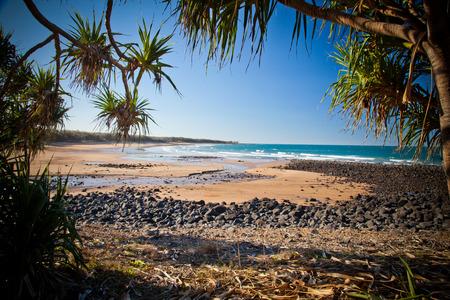 Rocky Sandy Beach and Sea Shore on a beautiful blue sky day. Photo is of Mon Repos Beach near Bundaberg, Australia