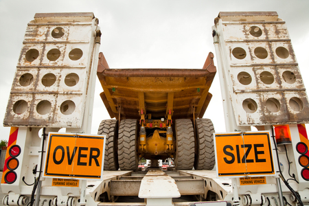 An over-sized yellow mining dump truck on a float trailer ready for transportation. Wide load. Stock Photo