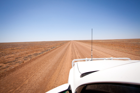 outback australia: A white four wheel drive with bullbar and aerial touring the arid dusty desert dirt track in Outback Australia