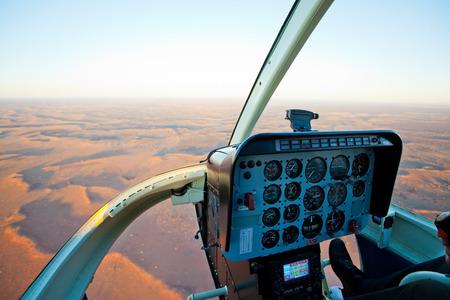 outback australia: Helicopter cockpit flying over desert outback Australia during sunset Stock Photo