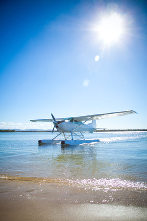 sunlight sky: Sea float plane approaching beach with rich blue sky and sun background