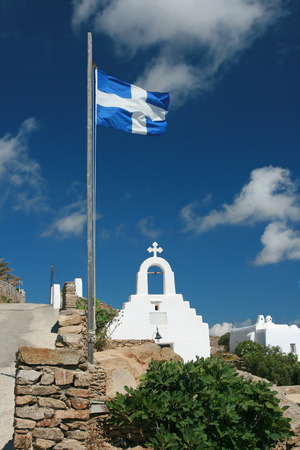 white wash: Mykonos Island - Greece. White Wash Chapel and Greek Flag Stock Photo