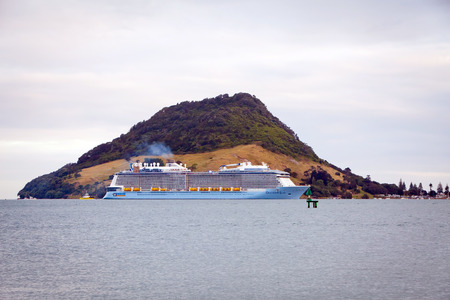 ovation: TAURANGA, NEW ZEALAND - DECEMBER 26, 2016: The mighty Ovation of the Seas Cruise Ship by Royal Caribbean International enters Tauranga Harbour for the very first time. Mount Maunganui in the background. Editorial
