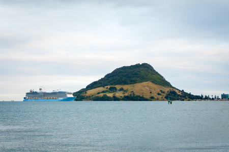 TAURANGA, NEW ZEALAND - DECEMBER 26, 2016: The mighty Ovation of the Seas Cruise Ship by Royal Caribbean International enters Tauranga Harbour for the very first time. Mount Maunganui in the background. Editorial