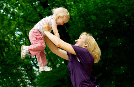 citypark: mother embrace her young daughter in the green citypark Stock Photo
