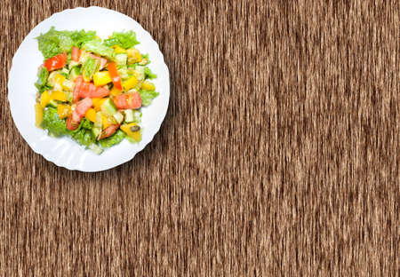Salad with tomato, pepper, pumpkin seeds on the white  plate on the wood table photo