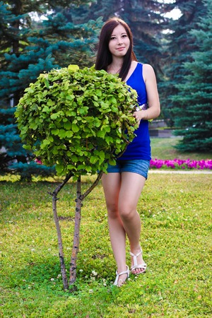 The beautiful girl in park against blossoming colours and decorative bushes Stock Photo