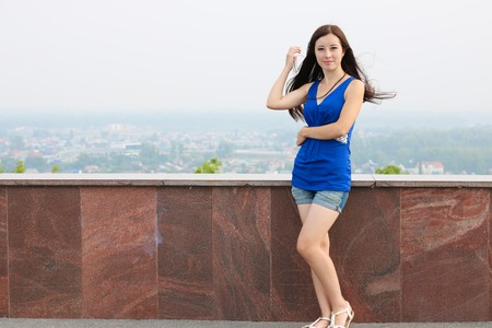 shapely legs: A young girl near the wall, but the background of the city.
