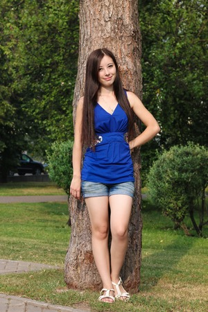 leaned: Young girl in shorts leaned against a tree in the Park. Stock Photo
