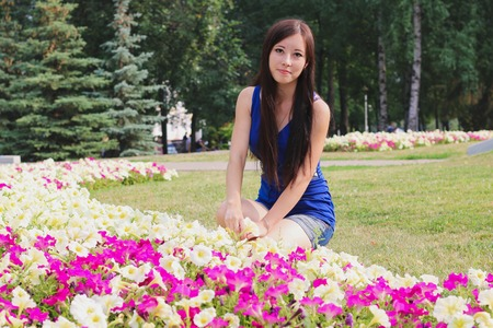 flowerbeds: Pretty girl sits near the flowerbeds. Outdoor.