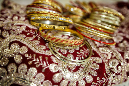 Gold Indian womens bracelets lie on a sari