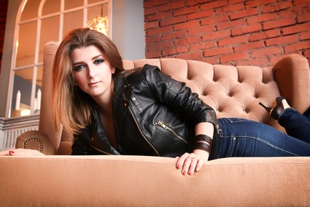 Charming girl in a leather jacket with high pumps lying on a sofa. slide movie.