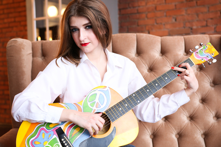 Girl in white shirt posing with a guitar in hippie style