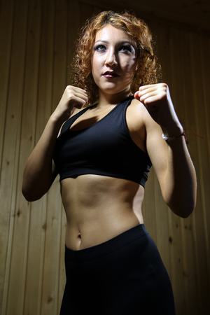Beautiful girl fighter standing in pose of boxer in sauna