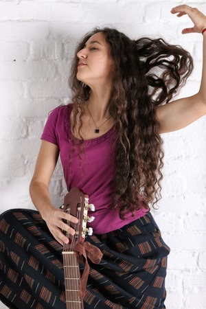 Young brunette woman with acoustic guitar in long skirt. Brick wall background