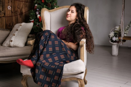 Young Hispanic woman sitting in chair in the rustic interior and waiting for celebration