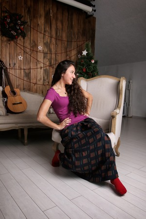 Young Hispanic woman sitting in chair in the Christmas interior and waiting for celebration