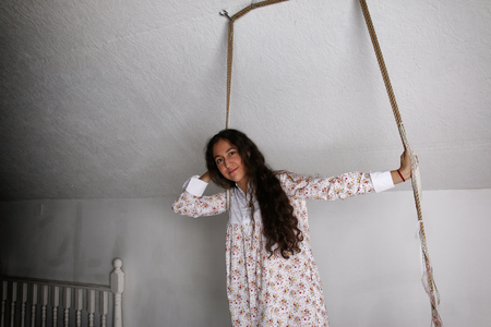 Portrait of young Hispanic woman in a nightgown on swing Banque d'images