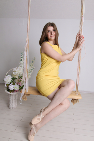 Young girl in yellow dress on swing in white room Banque d'images