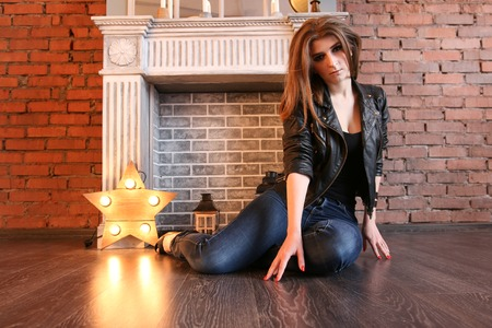 The girl in black leather jackets posing sitting on the floor Banque d'images