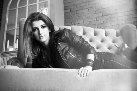 Charming girl in leather jacket with high pumps lying on a sofa Banque d'images