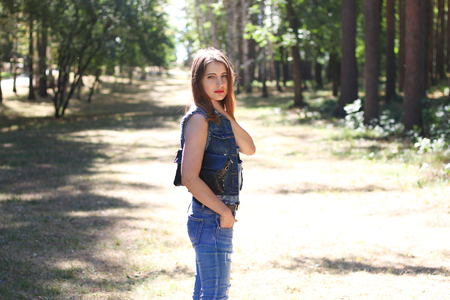 Young woman in ripped jeans in the forest