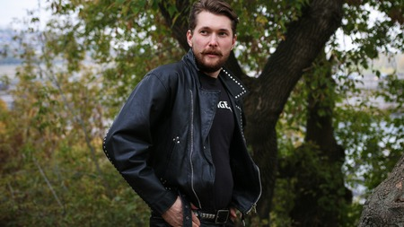 Bearded man in black leather jackets in a forest