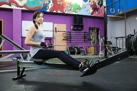 Young woman has on a trainer for back in the gym Banque d'images