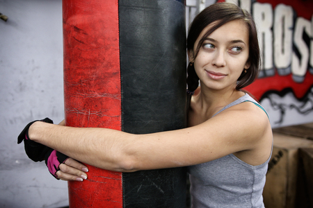 Attractive young woman hugging punching bag
