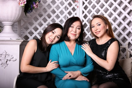 Asian family, mom and daughter in evening gowns sit on couch