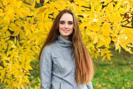 Beautiful young woman in leather jacket and black skirt posing in autumn park. Banque d'images