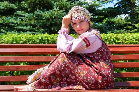 Young girl in Russian folk costume sits on the bench