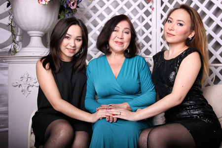 Asian family, mom and daughter in evening dresses sit on couch Banque d'images