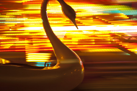 Plastic swan on the merry go round with blurred colored background. Photo taken 5. november 2014