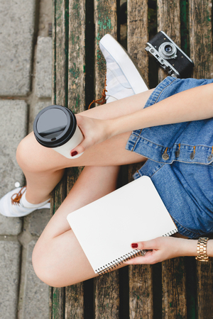 Young woman, wearing in blue shorts and sneakers, sitting on a wooden bench with cup of coffee and notebook, with retro camera on a background, close up. Point of view