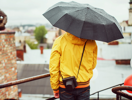 A young man in a yellow raincoat on the roof with an umbrella and old camera, on a rainy day on the background of the old city, rear view