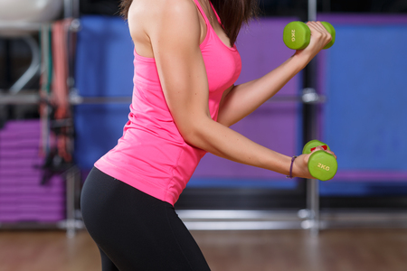 Muscled girl, wearing in pink shirt and black leggings, doing exercises with green dumbbells, on a sports equipment background, at the gym, close up