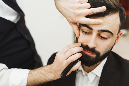 Man's hands wearing white shirt making a beard form with scissors for man with black hair at barber shop, portrait, close up.