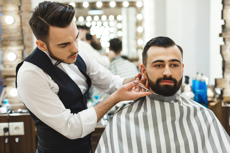 Handsome dark haired man wearing white shirt making beard form with scissors for man with black hair at barber shop, mirror at background. Stockfoto