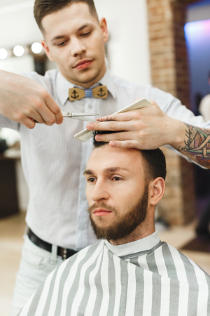 Attractive dark haired man with tattoo wearing white shirt doing a haircut for man with black hair at barber shop, mirror at background. Banco de Imagens