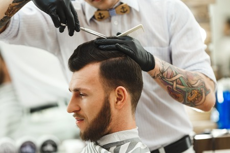 Barber wearing white shirt, watch and black gloves doing a haircut for client with scissors at barber shop, close up portrait, tattoo.