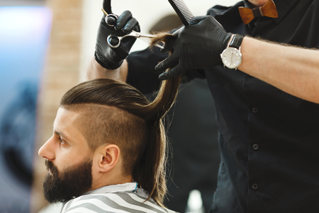 Mans hands in black gloves wearing watch doing a haircut with scissors for man with dark long hair and beard at barber shop, close up portrait, copy space.