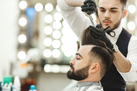 Handsome barber with dark hair wearing white shirt, watch and black gloves doing a haircut for client with scissors at barber shop, lights at background, copy space. 写真素材