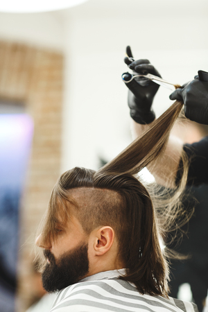 Man's hands in black gloves doing a haircut with scissors for man with dark long hair and beard at barber shop, close up portrait, copy space.