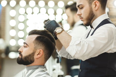 Stylish barber with dark hair wearing white shirt, watch and black gloves doing a haircut for client with scissors at barber shop, lights at background. 写真素材