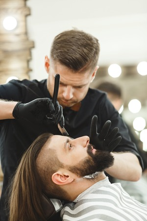 Barber in black shirt and gloves gloves making a beard form with razor for man with dark hair and beard at barber shop, portrait, close up.