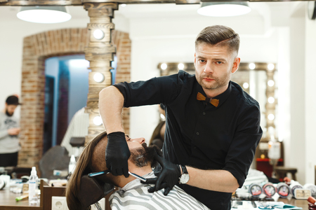 Dark haired man wearing black shirt and gloves making beard form with razor for man with black hair at barber shop, copy space, mirrors, portrait.