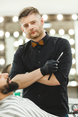 A portrait of handsome dark haired man wearing black shirt and gloves holding a razor at barber shop and looking at camera, mirrors at background.