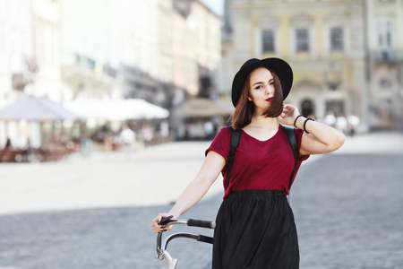 Beautiful girl in burgundy shirt, black skirt and hat with bag looking at camera. Standing near bicycle. Cycling, outdoor, city 写真素材
